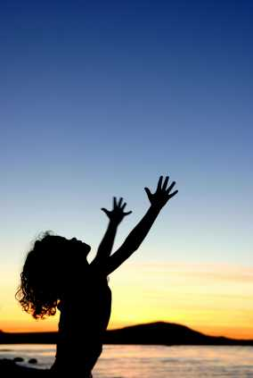 Image: Woman in sunset with raised outstretched arms