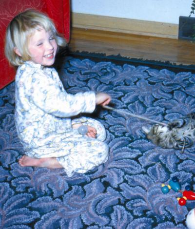 A photo of a child playing with a cat